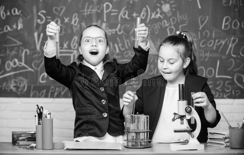 女孩校服繁忙与证明他们的假说 学校实验 r 有的健身房学生 免版税库存照片