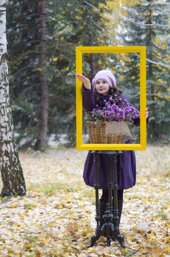 女孩框架的和在森林,捉住在棕榈的第一雪  免版税库存照片
