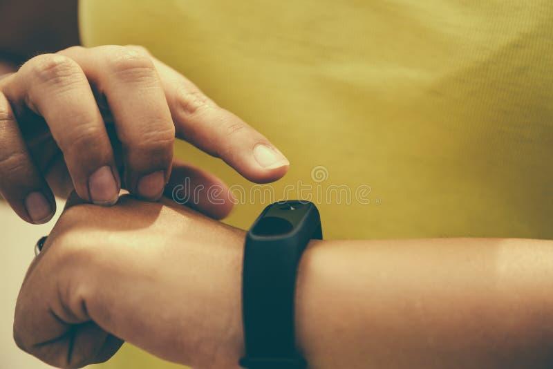 女孩检查在健身镯子或活动跟踪仪计步器的脉冲在腕子、体育、技术和健康生活方式概念 库存图片
