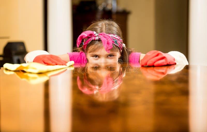 女孩检查桌表面的清洁房子画象  免版税库存照片
