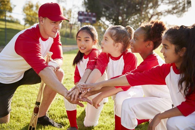 女孩棒球队下跪与他们的教练的,感人的手 免版税库存照片
