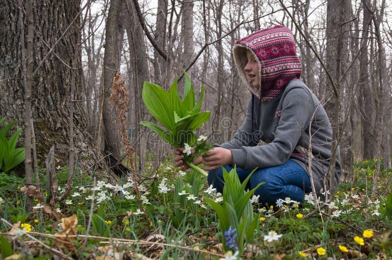 女孩森林发现和裁减的儿童少年snowdrops第一朵花  图库摄影