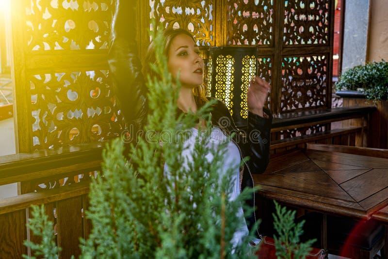 女孩模型是摆在时兴在咖啡馆与屏幕和灯在背景和与绿色植物前景的 免版税图库摄影