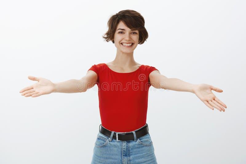 女孩欢迎微笑亲爱的客人涂手斜向一边广泛地招呼朋友要给热情的拥抱拥抱愉快 免版税库存图片