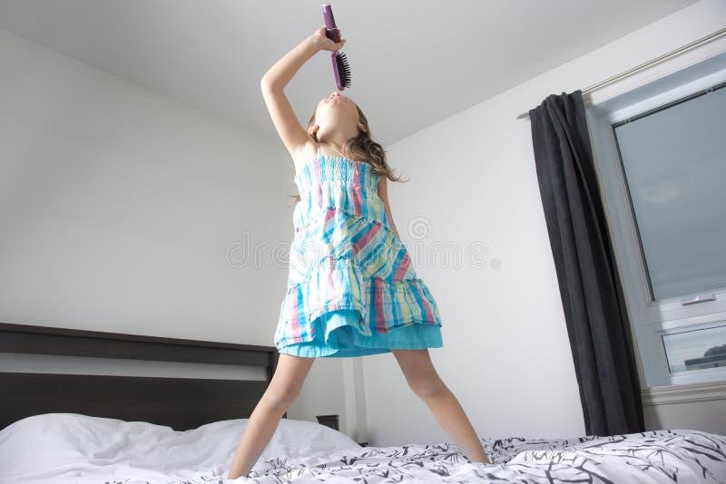 女孩歌手在卧室 免版税库存图片
