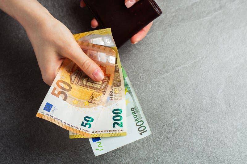 女孩正从棕色皮皮夹里取出一张50欧元的钞票。手,钱和钱包特写。慈善。灰色背景。手拿着50欧元 库存照片