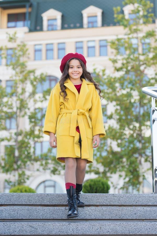 女孩步行defocused背景 迷人的矮小的法国样式时兴的女孩 帽子辅助法国时尚细节 孩子 库存图片