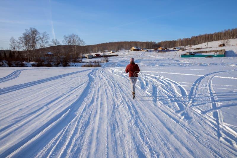 女孩沿在一个冻湖的一条冬天路跑往小山的一个村庄,在一冬天好日子 免版税图库摄影