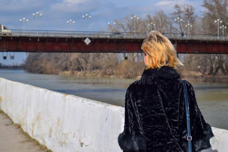 女孩沿堤防走到桥梁 回到视图 沿堤防的春天步行 免版税库存图片