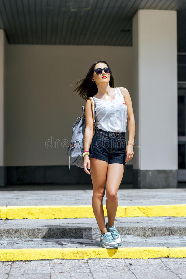 女孩浅黑肤色的男人在夏天在有休息简而言之和白色女衬衫太阳镜,时尚生活方式的背包的公园 免版税库存图片