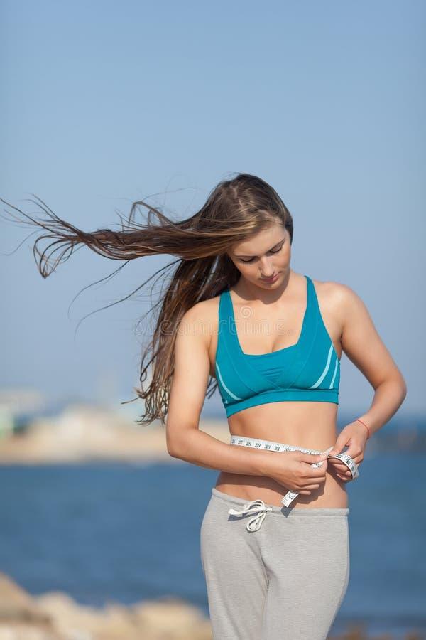 女孩测量看她的腰部下来 库存图片