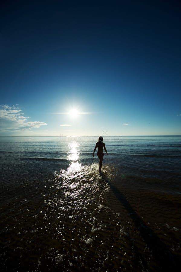 女孩海运剪影走的年轻人 免版税库存图片