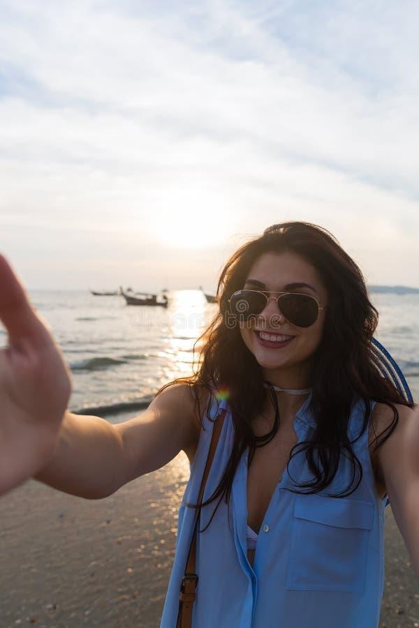 女孩海滩暑假,少妇采取Selfie照片日落 库存图片