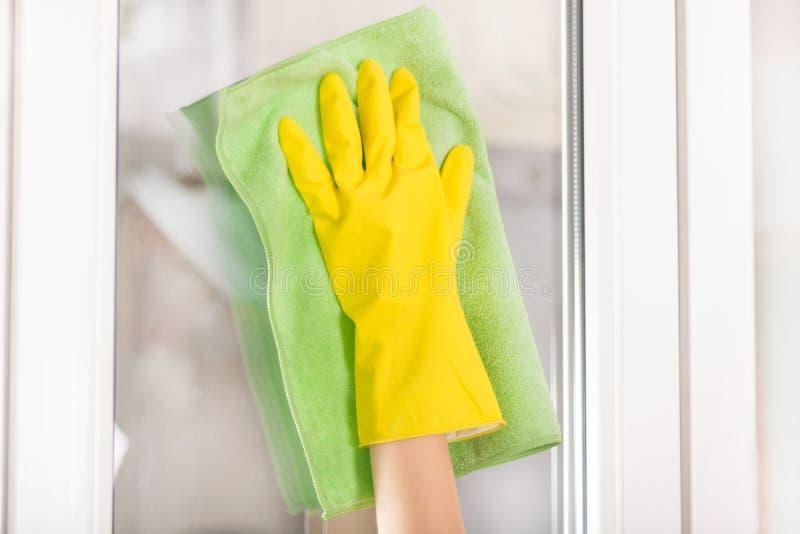 女孩清洁窗口在家与绿色旧布和黄色防护手套 免版税库存照片