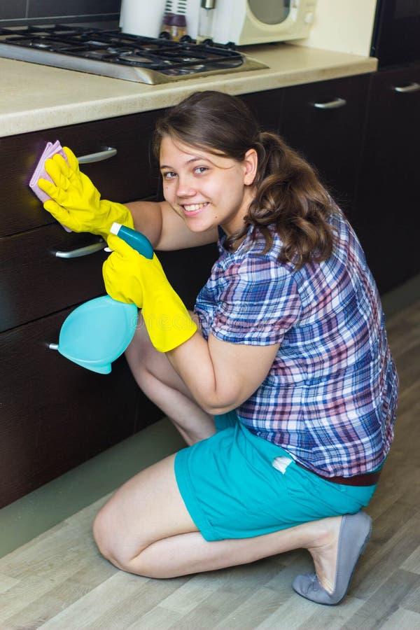 女孩清洁家具在厨房里 免版税图库摄影
