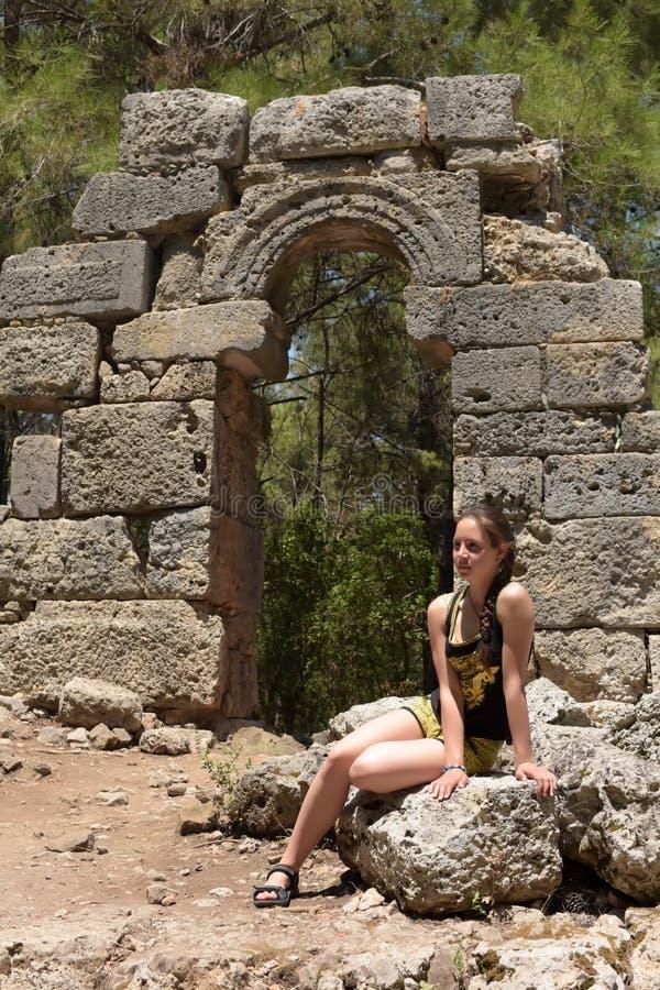女孩游人在反对古老废墟背景的夏天  免版税库存图片