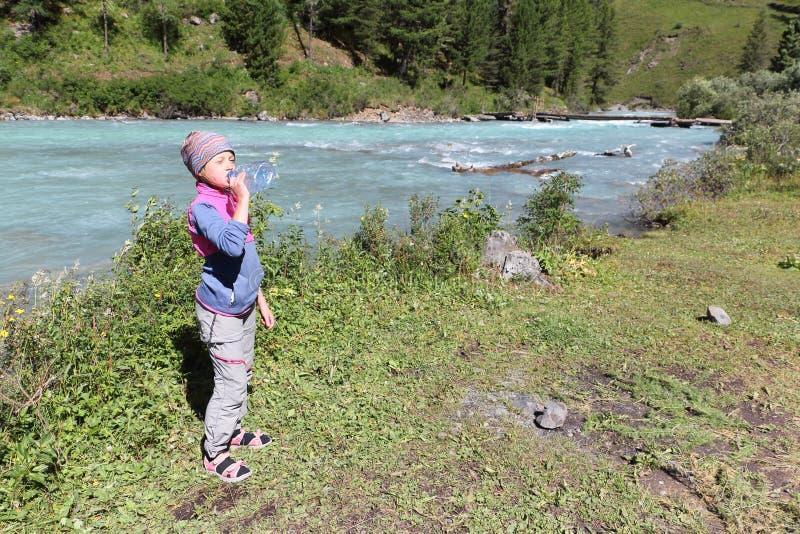 女孩游人在河附近喝从塑料瓶的水 免版税库存照片