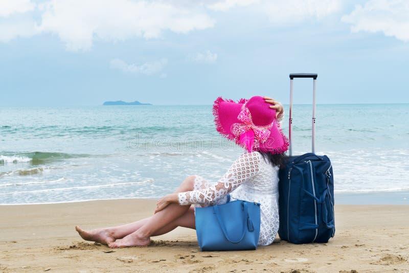 女孩游人坐与行李袋子的海滩 免版税库存图片