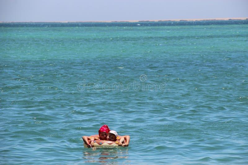 女孩游泳在说谎在可膨胀的圈子的海在度假夏天休假 库存照片