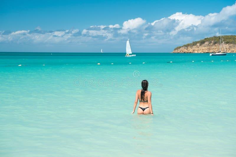 女孩游泳衣天蓝色的水晶海洋水背面图 假期豪华海洋海滩胜地 游泳通过不可思议的绿松石 免版税库存图片