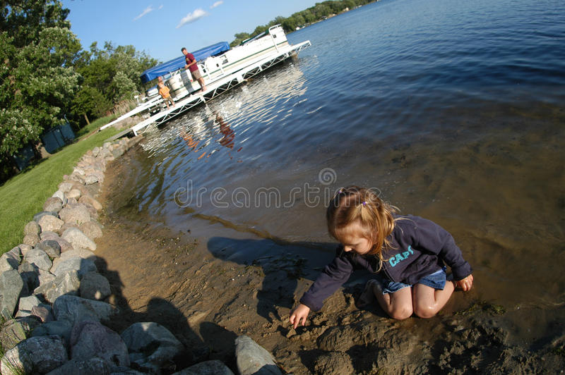 女孩湖边使用 免版税库存照片
