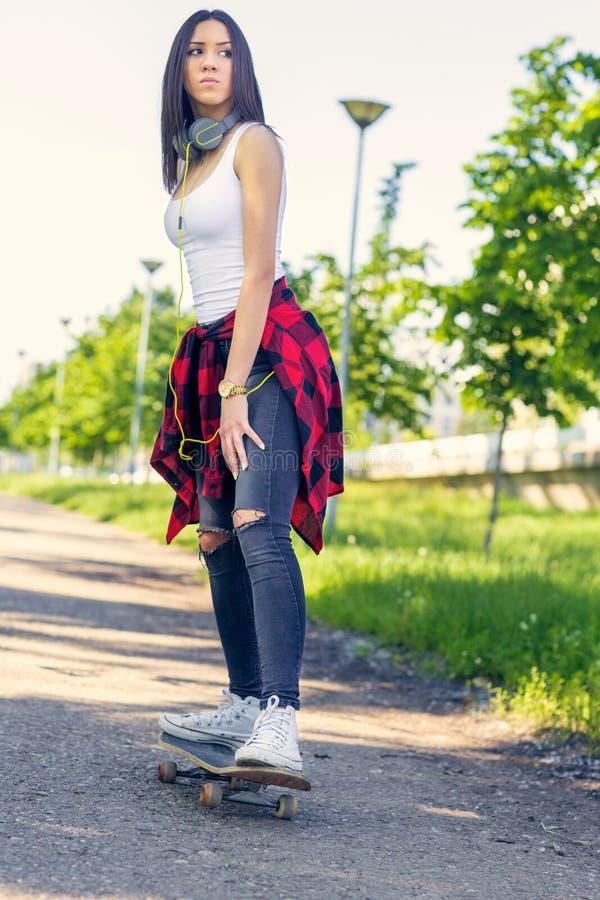 女孩溜冰板者-踩滑板在公园的运动的腿 库存图片