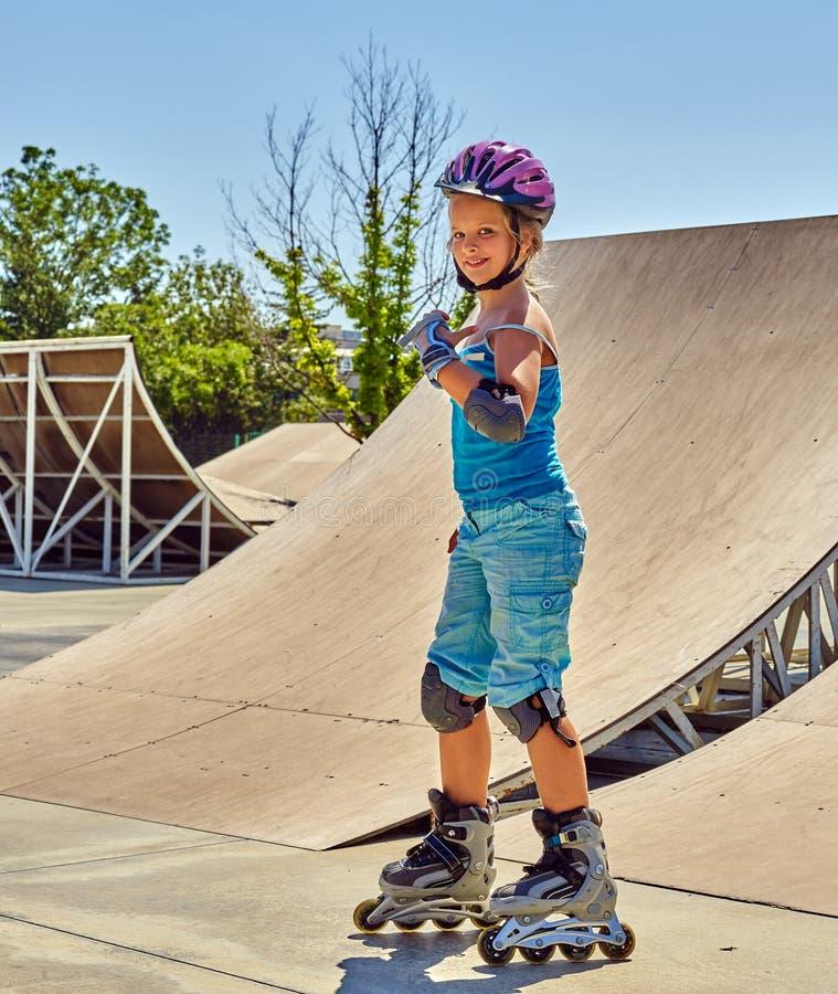 女孩溜冰鞋盔甲走的公园 在溜冰鞋的儿童骑马 库存照片