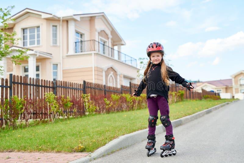 女孩滑旱冰在街道 免版税库存照片