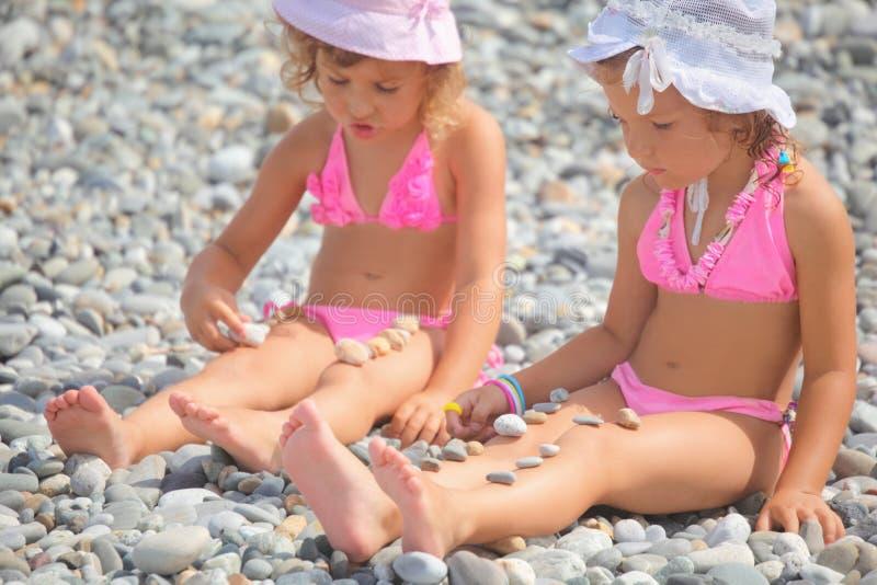 女孩演奏石头二的少许小卵石 免版税库存照片