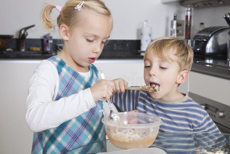 女孩烘烤曲奇饼,当兄弟品尝面团在厨房里时 免版税图库摄影