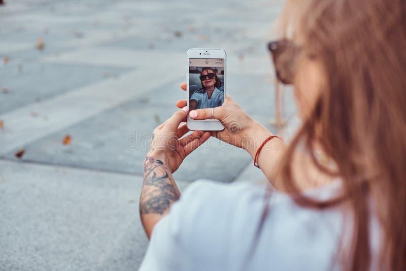 女孩特写镜头照片太阳镜的做一selfie户外 免版税图库摄影