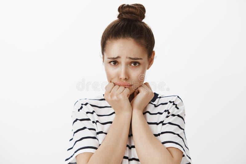 女孩犯了错误,请求饶恕,感到抱歉 有小圆面包发型的生气担心的美丽的妇女,举行 图库摄影