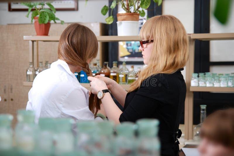 女孩猪尾把化学班的学生编成辫子 免版税图库摄影