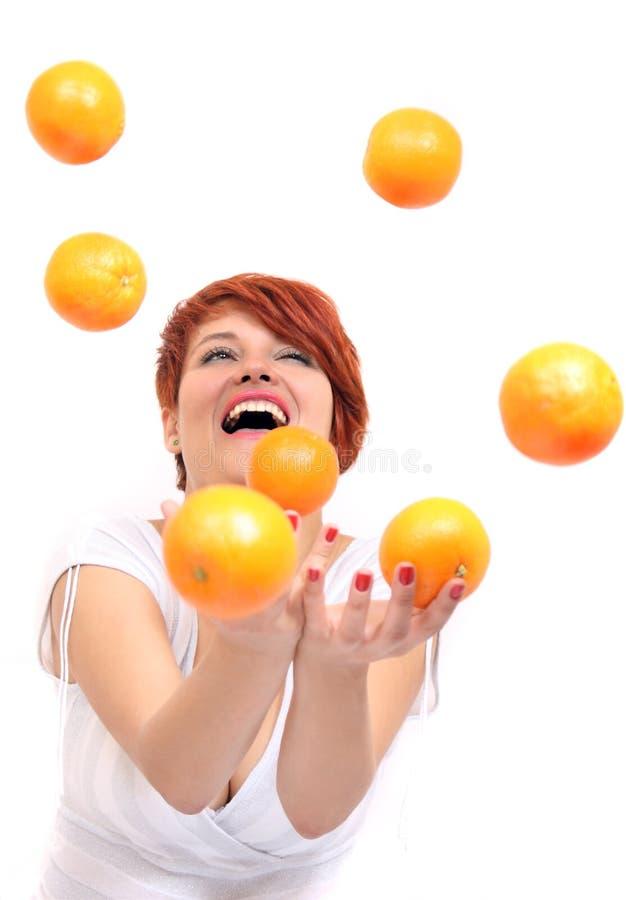 女孩玩杂耍的桔子 免版税图库摄影