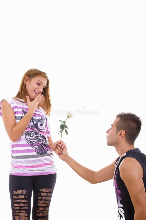 给女孩玫瑰的年轻人 免版税库存照片