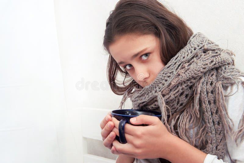 女孩生病并且喝茶 免版税图库摄影