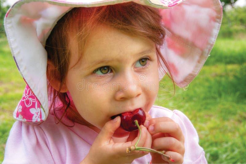 女孩用一个甜樱桃 库存照片