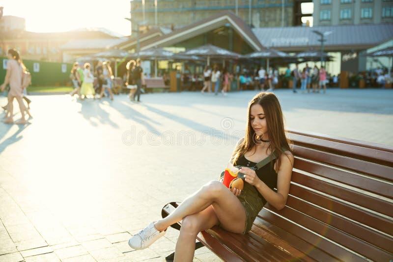 女孩用乳酪汉堡和炸薯条在她的手上坐o 免版税库存照片