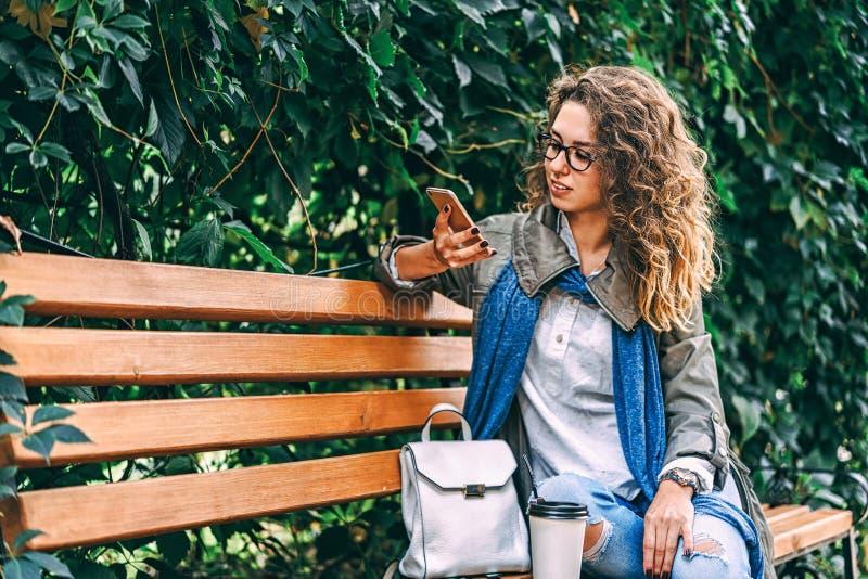 女孩用卷发饮料的咖啡和室外用途的智能手机 免版税图库摄影