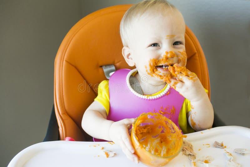 女孩用在她的面孔的食物 免版税库存图片