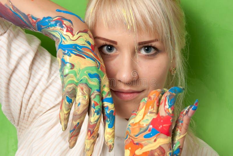 女孩用在新鲜的油漆的手 免版税图库摄影