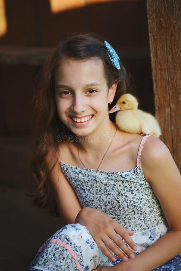 女孩用小的黄色鸭子在夏天村庄 库存照片