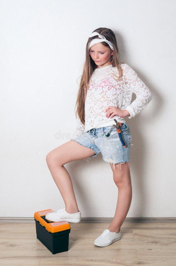 女孩用工具加工年轻人 免版税图库摄影
