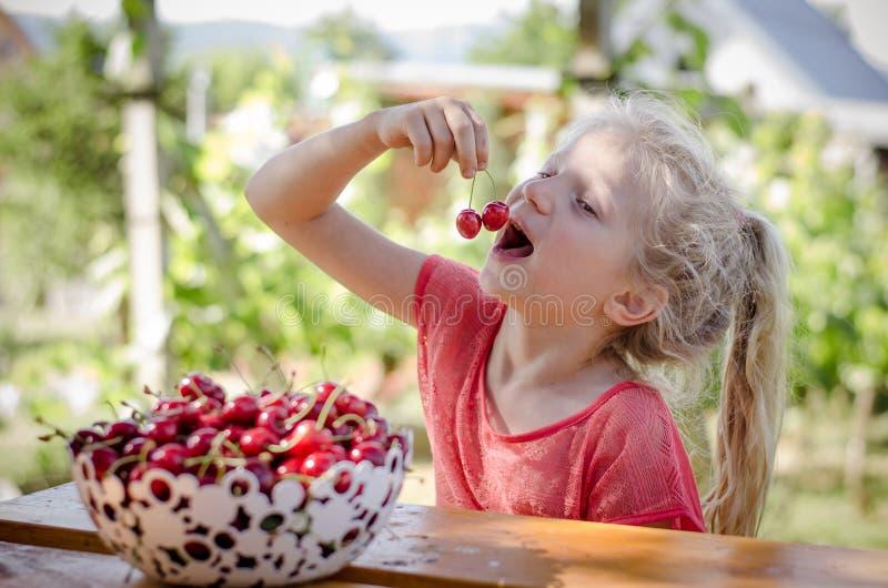 女孩用成熟红色樱桃果子 图库摄影