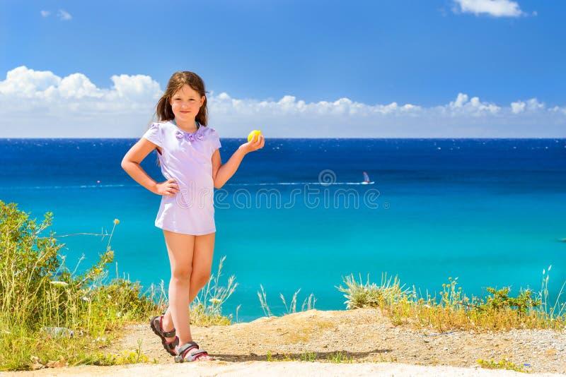 女孩用摆在反对克里特岛海的柠檬 巴厘岛 库存图片