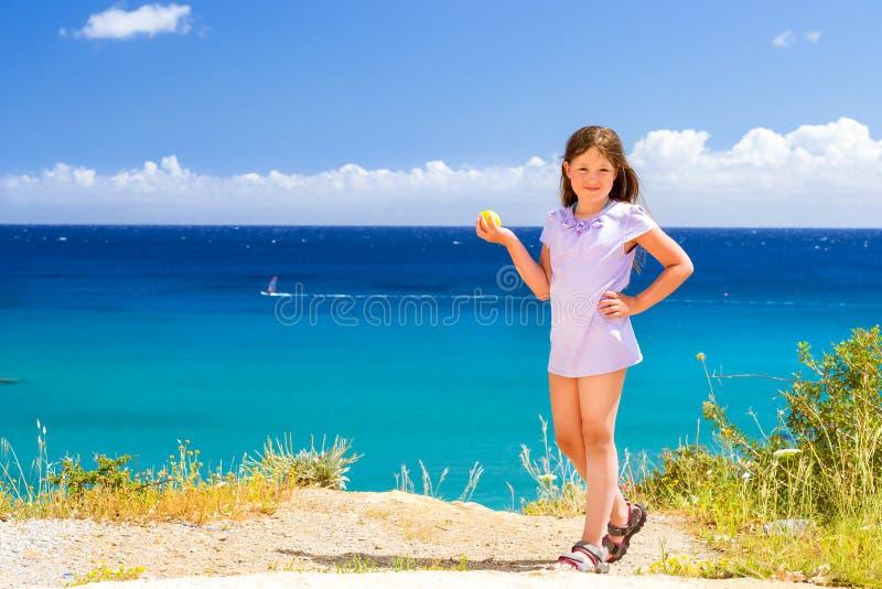 女孩用摆在反对克里特岛海的柠檬 巴厘岛 图库摄影