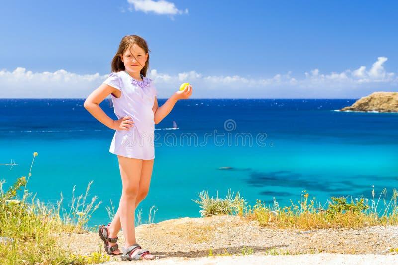 女孩用摆在反对克里特岛海的柠檬 巴厘岛 免版税库存图片