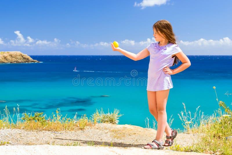女孩用摆在反对克里特岛海的柠檬 巴厘岛 免版税图库摄影