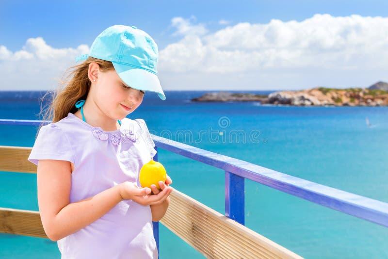 女孩用摆在反对克里特岛海的柠檬 巴厘岛 免版税库存照片