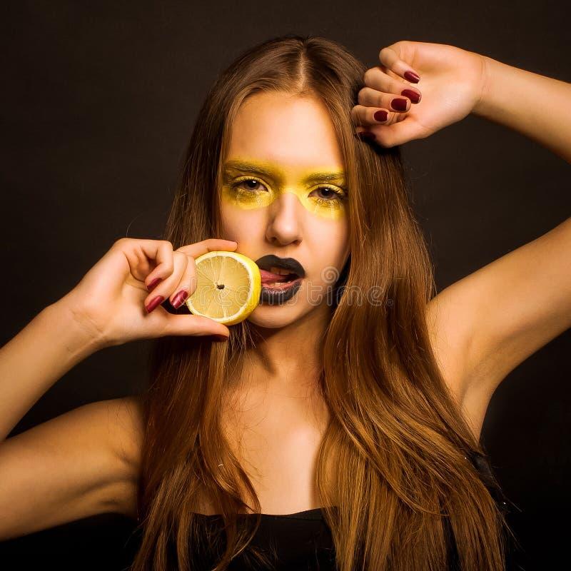 女孩用柠檬 库存照片